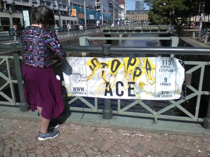 Kvinna protesterar motden militära flygövningen Arctic Challenge.