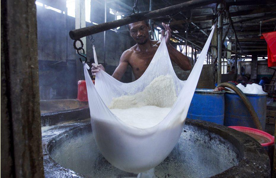 Tofumassan rinner av i en silduk på en liten tofufabrik på Bali.