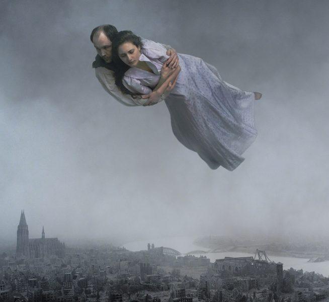 """Ett par som svävar över en bombad stad är en av många märkliga och surrealistiska scener i Roy Anderssons nya film """"Om det oändliga"""" som hade premiär i fredags."""
