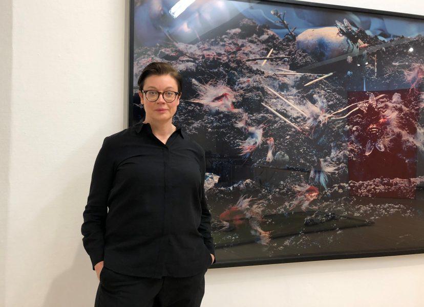Anna Johansson, curator på Malmö konstmuseum framför ett fotografi av Cindy Sherman.