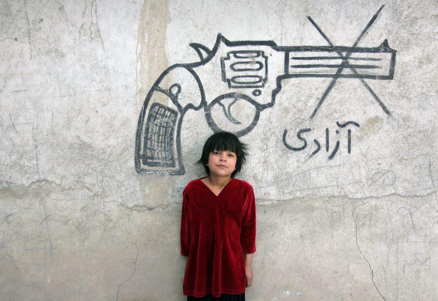 """Ett barn syns bredvid en väggmålning med ordet """"frihet"""", i Afghanistans huvudstad Kabul."""