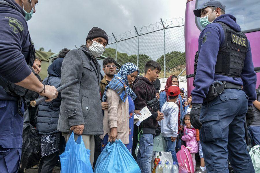 Migranter står uppställda utanför Morialägret på Lesbos.