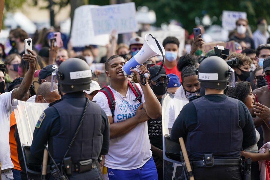 Demonstranter i Kenosha, Wisconsin, protesterar mot att polisen i söndags sköt en svart man framför hans barn.