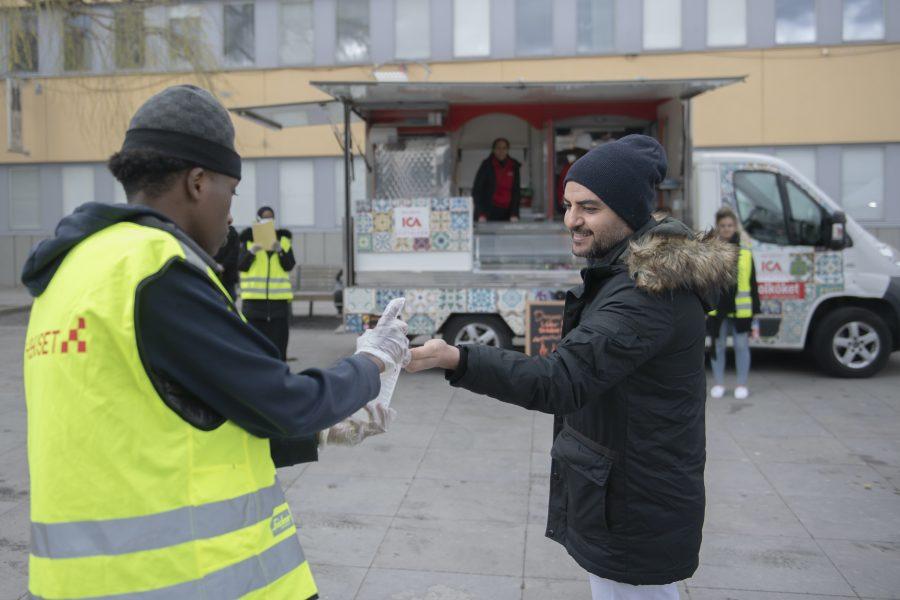 Ungdomsvolontärer i samarbete med Fryshuset delar ut gratis mat och informerar om coronaviruset och Covid-19 på olika språk i Tensta centrum.