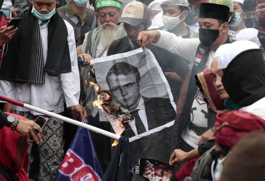 Ett porträtt av president Emmanuel Macron bränns under en antifransk demonstration i Jakarta i Indonesien på måndagen.