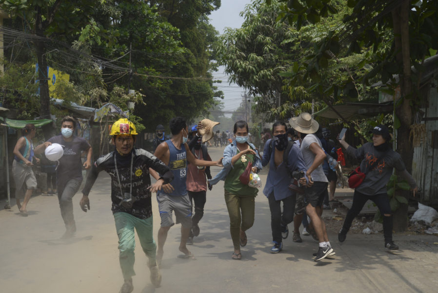 Demonstranter flyr militären efter en demonstration i Rangoon i tisdags.
