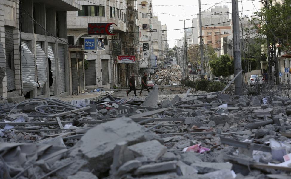 Människor inspekterar resterna av en bombad kommersiell byggnad och en vårdklinik i staden Gaza.
