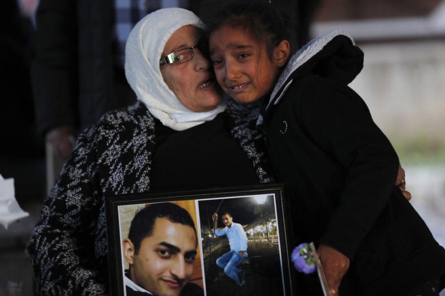En flicka kramar om sin farmor, som bär på porträtt av en son som omkom i hamnexplosionen i augusti i fjol.